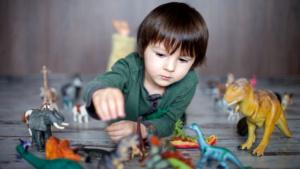 bambino che gioca con dinosauri giocattoli colorati